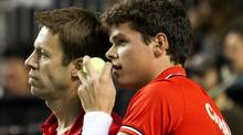Canada's Daniel Nestor (L) and Milos Raonic talk while their doubles team plays against France during the Davis Cup tennis match in Vancouver, British Columbia February 11, 2012. REUTERS/Ben Nelms (Ben Nelms/Reuters)