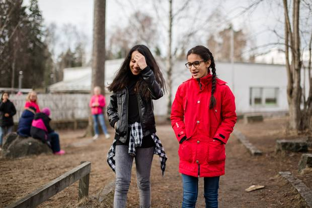 Sabrina Essed, 12, walks with Lara Osman during recess.