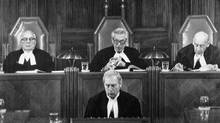 Justice Ronald Martland, left, and Justice Roland Ritchie, right, listen to Chief Justice Bora Laskin read the Supreme Court's decision on the federal government's constitutional package in Ottawa on Oct. 3, 1981. (Fred Chartrand/CP)