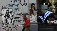 A man walks past a wall covered with graffiti in central Athens on June 19, 2012. (Pascal Rossignol/Reuters)