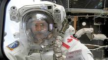 US space shuttle Endeavour astronaut Canadian Chris Hadfield peers in a shuttle window, 22 April 2001, after successfully setting up the Canada Arm 2 on the Destiny module of the International Space Station during first spacewalk. (AFP PHOTO/NASA PHOTO/AFP PHOTO/NASA PHOTO)