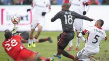 D.C. United's goalkeeper Bill Hamid (left) tips away a goal bound effort from Toronto FC 's Jermain Defoe (centre) as Untied's Sean Franklin closes during first half MLS action in Toronto on Saturday March 22, 2014. (Chris Young/THE CANADIAN PRESS)
