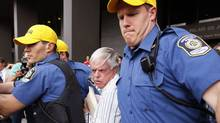 Financial adviser Earl Jones is rushed out of the courthouse in Montreal, July 28, 2009. (SHAUN BEST/REUTERS)