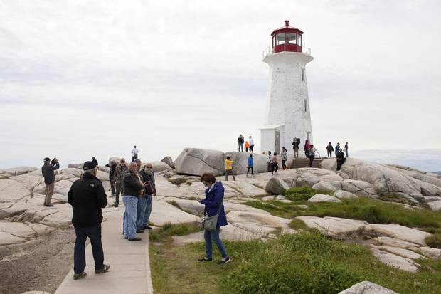 Peggys Cove, N.S.: The travellers mill around the Peggys Point lighthouse in Nova Scotia's St. Margarets Bay.