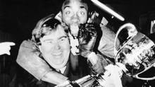 """Toronto Argonauts Raghib """"Rocket"""" Ismail jumps on the back of team co-owner and actor John Candy while he was holding the Grey Cup during victory celebrations back in Toronto after the game. The Toronto Argonauts had defeated the Calgary Stampeders 36-21 in the annual fall classic held at Winnipeg Stadium Nov. 24, 1991. Chris Schwarz / REUTERS (Chris Schwarz/REUTERS)"""