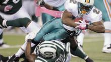 Miami Dolphins running back Reggie Bush (22) is tackled by New York Jets inside linebacker Bart Scott during the first quarter of an NFL game Monday, Oct. 17, 2011, in East Rutherford, N.J. (Julio Cortez/AP)