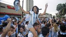 Soccer fans celebrate after Argentina defeated the Netherlands 4-2 in a penalty shootout (Wilfredo Lee/AP)