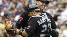 Toronto Blue Jays' Roy Halladay celebrates his complete game with catcher Rod Barajas against the Boston Red Sox in their MLB American League baseball game in Toronto, July 19, 2009. REUTERS/Mark Blinch (CANADA SPORT BASEBALL)
