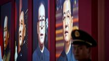 "A Chinese paramilitary policeman stands guard next to a display showing four generations of Chinese leaders, from right, current President Hu Jintao, former President Jiang Zemin, paramount leaders Deng Xiaoping and Mao Zedong during an exhibition entitled ""Scientific Development and Splendid Achievements"" held ahead of the 18th National Congress of the Communist Party of China in Beijing, Nov. 5, 2012. (Andy Wong/AP)"