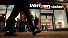 A pedestrian walks by as customers stand in line to purchase Apple Inc. iPhone 4 smartphones in front of a Verizon Wireless store in San Francisco, California, U.S., on Thursday, Feb. 10, 2011. Verizon Wireless is exploring the idea of conducting business in Canada. (Ryan Anson/Bloomberg)