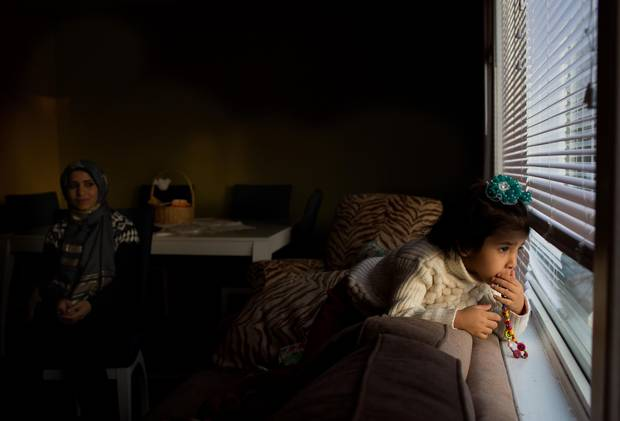 Karim Dalaa, 3, looks out the window at home as her mom Zamzam Dalaa looks on in Edmonton, Alberta in December 2015. The newly arrived refugees were sponsored by a local community group.
