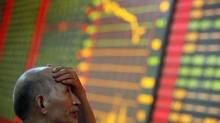 A stock investor reacts near a board displaying stock prices at a brokerage house in Huaibei in central China's Anhui province, Monday June 24, 2013. Global stock markets reeled Monday, with Shanghai's index enduring its biggest loss in four years. (AP)