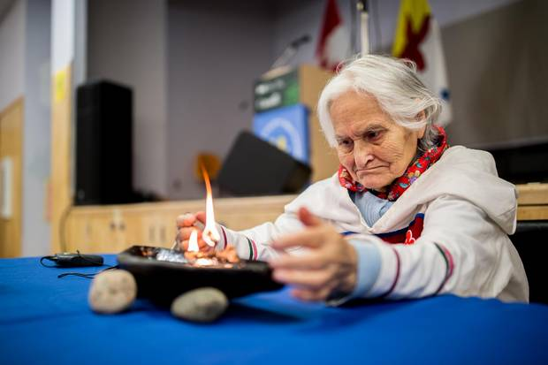 Elisapee Ootova, Jena Merkosak's grandmother, lights a qulliq before the announcement of the new protected area of Lancaster Sound.