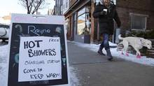 A man walks his dog past a spa advertising free hot showers for residents whose electricity remains knocked out by an ice storm, on Danforth Avenue in Toronto December 24, 2013. (CHRIS HELGREN/REUTERS)
