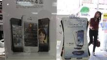Banner advertising Samsung's Galaxy S III and Apple's iPhone 4S are displayed at a mobile phone shop in Seoul, in this Aug. 27, 2012 photo. (Ahn Young-joon/AP Photo)