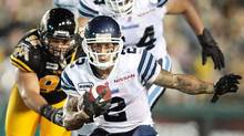 Chad Owens of the Toronto Argonauts avoids a tackle from Eddie Steele of the Hamilton Tiger-Cats in Canadian Football League action at Ivor Wynne Stadium in Hamilton, Ontario, Saturday, July 14, 2012. (Geoff Robins/THE CANADIAN PRESS)