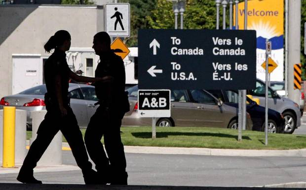Canadian border guards are silhouetted as they replace each at the Douglas border crossing in Surrey, B.C., on August 20, 2009.