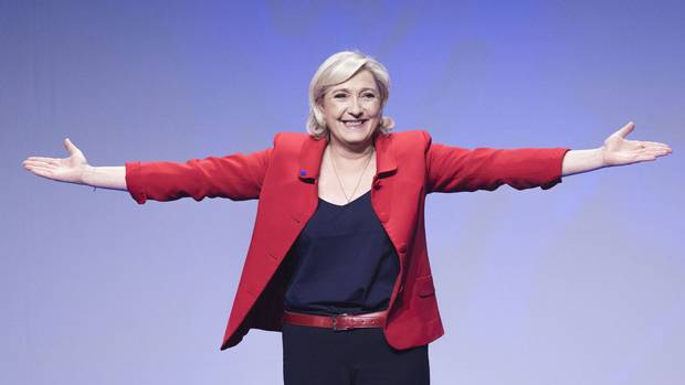 Marine Le Pen gestures as she arrives for a campaign meeting in Paris on April 17, 2017.