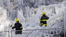 Emergency workers search through the frozen rubble of a seniors residence Friday, Jan. 24, 2014 in L'Isle-Verte, Que. (RYAN REMIORZ/THE CANADIAN PRESS)