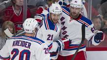 New York Rangers' Rick Nash (61) celebrates with teammates Chris Kreider (20) and Derek Stepan after scoring against the Montreal Canadiens during first period in Game 2 of the NHL Eastern Conference final Stanley Cup playoff action in Montreal, Monday, May 19, 2014. (Graham Hughes/THE CANADIAN PRESS)