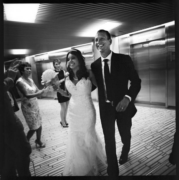As friends and family cheer, Denise Flores and Ryan Goodman walk through City Hall as a newly married couple.