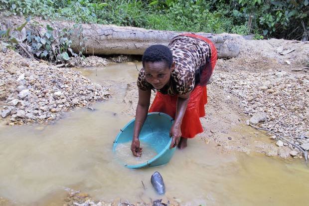 Bibicha Sanao pans for gold at a small mining site near the village of Metale in Ituri province, Democratic Republic of Congo. Small-scale mining is a huge source of income in many African countries, but female miners face widespread discrimination and cultural taboos.
