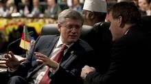 Prime Minister Stephen Harper speaks with Foreign Affairs Minister John Baird at the Commonwealth Heads of Government meeting in Perth, Australia, on Oct. 28, 2011. (Adrian Wyld/THE CANADIAN PRESS)