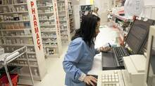 Debbie Cabrera fills a prescription at the Zellers pharmacy in Square One Mall, Mississauga, Ont. As Target Corp. prepares to take over Zellers properties, other drugstores are hoping to attract Zellers' pharmacy customers. (Brett Gundlock for The Globe and Mail/Brett Gundlock for The Globe and Mail)