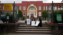 From left to right, teacher Caroline Lichimo, teacher librarian Lyse Cote, and Ginaya Peters, who teaches French immersion to special needs students, on the picket line outside Lord Tennyson Elementary School in Vancouver on June 17, 2014. (Darryl Dyck/The Canadian Press)