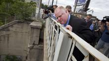 Toronto Mayor Rob Ford peers over the edge of the Dufferin Street Bridge June 5, 2013. Ford visited the bridge following an announcement that it will be closed for 18 months for much needed repairs. (Moe Doiron/The Globe and Mail)