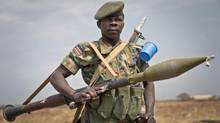 A South Sudanese government soldier stands guard at the airport in Malakal on Jan. 21, 2014. (Mackenzie Knowles-Coursin/Associated Press)