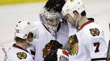 Chicago Blackhawks goalie Corey Crawford (50) is congratulated by teammates Brent Seabrook (7) and Brian Campbell (51) after the Blackhawks beat the St. Louis Blues 5-3 in an NHL hockey game Monday, Feb. 21, 2011, in St. Louis. (AP Photo/Tom Gannam) (Tom Gannam)