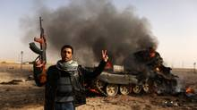 A Libyan rebel flashes a V-sign in front of burning tank belonging to loyalist forces bombed by coalition air force in the town of Ajdabiya on March 26, 2011 as forces loyal to Libyan leader Moamer Kadhafi were retreating after rebels recaptured the key eastern town in their first significant victory since the launch of the Western-led air strikes a week ago. (Patrick Baz/AFP/Getty Images/Patrick Baz/AFP/Getty Images)