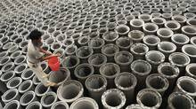 A labourer splashes water on newly-made pipes at a cement plant in Yingtan, Jiangxi province. Infrastructure projects are booming in China thanks to the government's 4-trillion yuan stimulus package. Plans to build sewers, roads and bridges have all been accelerated to boost the economy. (STRINGER SHANGHAI/Reuters)