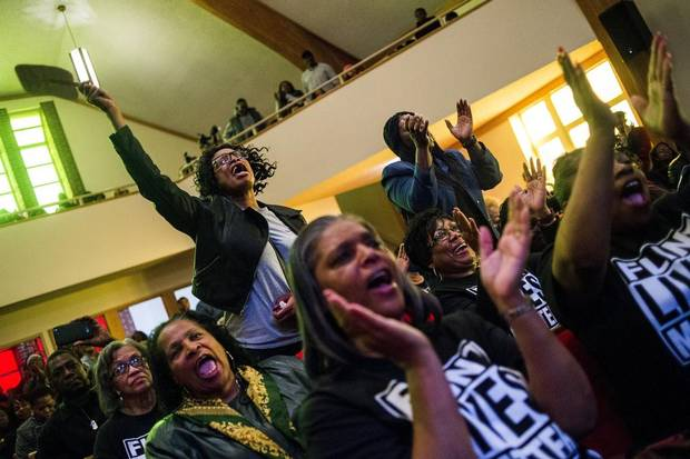 Flint resident Sharon Moore, left, leaps up to shout out her support as she listens to pastor David Bullock during a town hall meeting packed with more than 500 people to discuss the ongoing Flint water crisis on Monday, Feb. 1, 2016 at First Trinity Missionary Baptist Church in Flint, Mich.