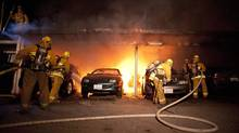 Los Angeles Fire Department firefighters extinguish numerous fires in a carport in the Sherman Oaks neighborhood of Los Angeles on Monday, Jan. 2, 2012. (Dan Steinberg/ The Associated Press/Dan Steinberg/ The Associated Press)