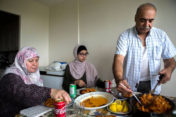 Mr. Sharbaji serves up a traditional eal from Aleppo with Sedra and his wife, Mouna, left.