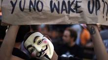 A demonstrator wearing a Guy Fawkes mask holds a banner during a protest at the Portuguese parliament as part of the United for Global Change movement in Lisbon October 15, 2011. (RAFAEL MARCHANTE/REUTERS/RAFAEL MARCHANTE/REUTERS)