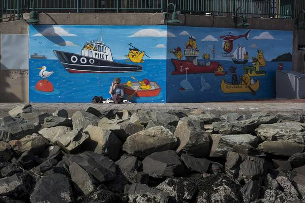 A woman rests near a nautically themed mural near a rock breakwall along the Halifax waterfront.