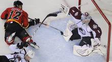 Calgary Flames' Jarome Iginla (12) is knocked down in front of Colorado Avalanche's goalie Semyon Varlamov (R) by Ryan O'Byrne during the third period of their NHL hockey game in Calgary, Alberta March 30, 2012. REUTERS/Todd Korol (Todd Korol/Reuters)