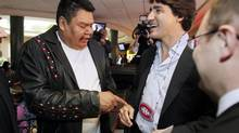 David Spence from Nisichawayisihk Cree Nation gives Justin Trudeau a beated Montreal Canadiens necklace as the Liberal Leader visits a food court in downtown Winnipeg on May 2, 2013. (JOHN WOODS/THE CANADIAN PRESS)