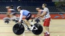 Canada coach Richard Whooles assists Tara Whitten during cycling training for the 2012 Summer Olympics, Monday, July 30, 2012, in London. (Sergey Ponomarev/AP)