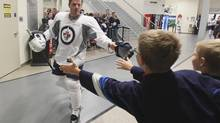 Winnipeg Jets' Ian White (7) reaches out to a young fan on the second day of NHL hockey training camp Thursday, September 12, 2013 in Winnipeg. (JOHN WOODS/THE CANADIAN PRESS)