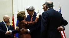 U.S. Secretary of State John Kerry, third from right, hugs European Union foreign policy chief Catherine Ashton after she delivered a statement during a ceremony in Geneva on Nov. 24, 2013. (Denis Balibouse/Reuters)