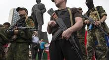 Armed pro-Russian separatists stand in front of the monument to Vladimir Lenin before take an oath the city of Donetsk June 21. (SHAMIL ZHUMATOV/REUTERS)