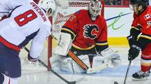 Calgary Flames goalie Karri Ramo (31) makes a save against a shot from Washington Capitals right wing Alex Ovechkin (8) as Calgary Flames defenceman T.J. Brodie (7) defends during the second period at Scotiabank Saddledome. (Sergei Belski/USA Today Sports)