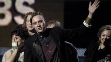 Win Butler, center, is joined by fellow band members of Arcade Fire to accept the award for album of the year at the 53rd annual Grammy Awards on Sunday, Feb. 13, 2011, in Los Angeles. (MAtt Sayles/AP)
