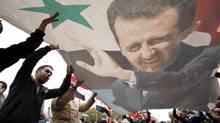 Pro-regime protesters shout slogans and wave a portrait Syrian President Bashar Assad during a demonstration in Damascus on Jan. 11, 2012. (Muzaffar Salman/AP)