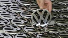 File picture shows an employee posing with an emblem for a Volkswagen Golf car during a photocall in a production line at the Volkswagen headquarters in Wolfsburg November 14, 2008. (CHRISTIAN CHARISIUS/REUTERS)