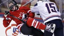Canada's Gillian Apps, left, is hit by United States' Anne Schleper (15) during the third period of a Four Nations Cup women's hockey game on Wednesday, Nov. 6, 2013, in Lake Placid, N.Y. (Mike Groll/AP)